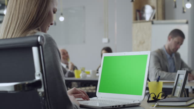 Women working on laptop with green screen at office