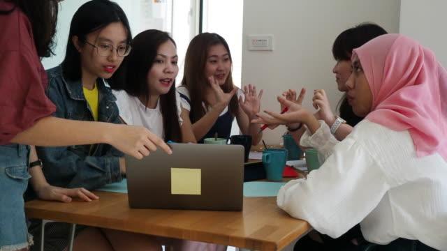 vídeos de stock, filmes e b-roll de mulheres que trabalham junto com o portátil, a tabuleta e os blocos notas - coworking space
