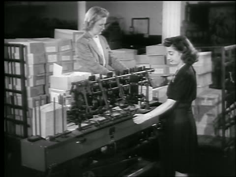 b/w 1944 2 women working with machine using war bonds / boxes in background / world war ii / newsreel - 1944 stock videos and b-roll footage