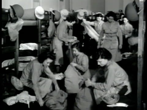 vídeos de stock, filmes e b-roll de women's army corps wacs packing duffel bags in barracks wacs in uniform skirts helmets carrying duffles over shoulders climbing up into back of... - 1943