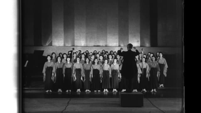 vidéos et rushes de a women's chorus sings the empressís verse ìmay the fellow warrior's spirits rest in peaceöî disabled japanese servicemen exercise learn industrial... - choeur