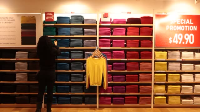 women's clothing at a uniqlo co store on 5th avenue in new york us on tuesday jan 21 wide shot of colorful sweatersfolded on shelves close up of... - flagship store stock videos and b-roll footage