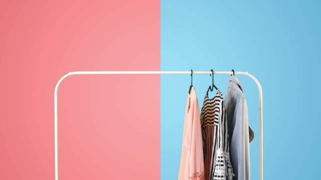 Women's clothing on a white clothes hanger on pink and blue pastel colors background.