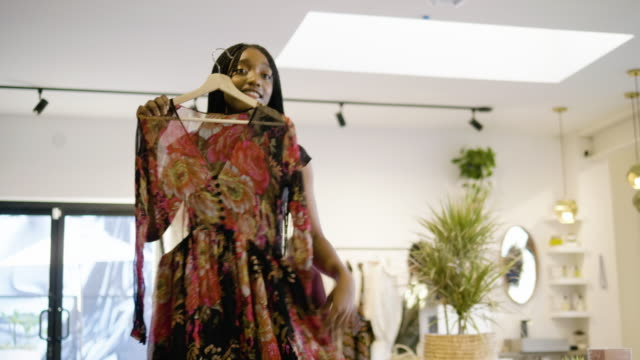A women's clothing store owner looks at clothing samples a fashion designer is selling to her
