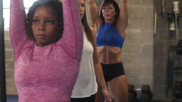 women's fitness class doing dumbbell squats in gym - sich verschönern stock-videos und b-roll-filmmaterial