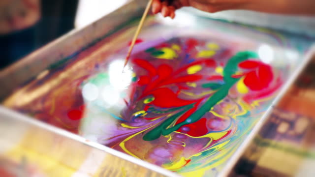 women's hand drawing with a needle on the water for creating ebru marbling art. - drawing art product stock videos & royalty-free footage