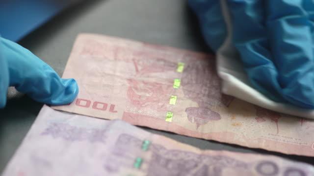 コロナウイルスcovid-19を洗浄するための紙幣を拭く手袋のecu女性の手 - 衛生管理点の映像素材/bロール