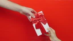 Women's hand is giving gift holiday box with red bow on red background. Female hand gives gift in festive box with red satin bow to male hand. St. Valentine's Day, Birthday Holiday