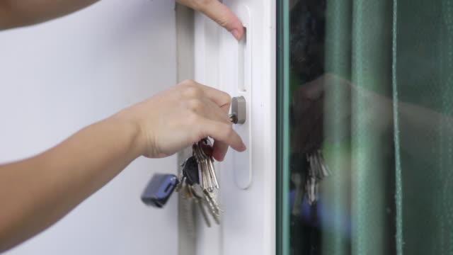 女性の手自宅で玄関をロックし、ロックを解除します。 - 玄関のドア点の映像素材/bロール
