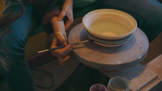 cu women's hand painting a bowl on her potter's wheel - art studio stock videos & royalty-free footage