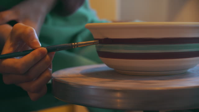 cu women's hand painting a bowl on her potter's wheel - pottery stock videos & royalty-free footage