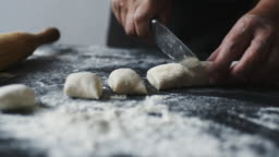 Women's hands cut the dough into pieces with kitchen knife