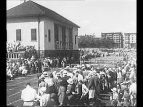 "women's hurdle race in jersey city, nj, in 1931; camera follows as women race past audience; mildred ""babe"" didrikson, at right, wins / didrikson... - atletico video stock e b–roll"