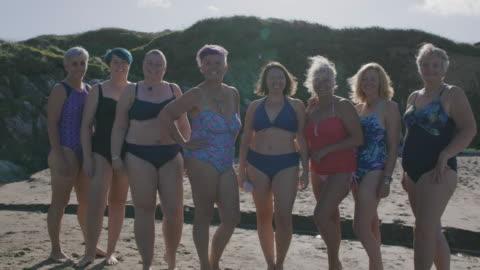 vídeos y material grabado en eventos de stock de un club de natación para mujeres que se ríen juntas mientras se alinean para una fotografía de grupo en una playa vacía. - vinculación
