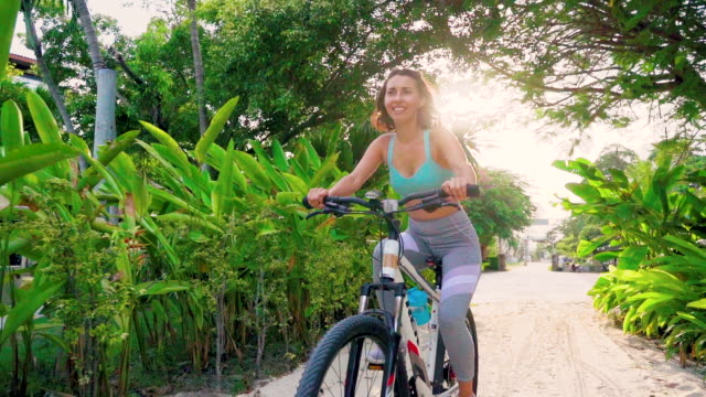 wonan riding bicycle in slow motion on the beach - ko samui stock videos & royalty-free footage