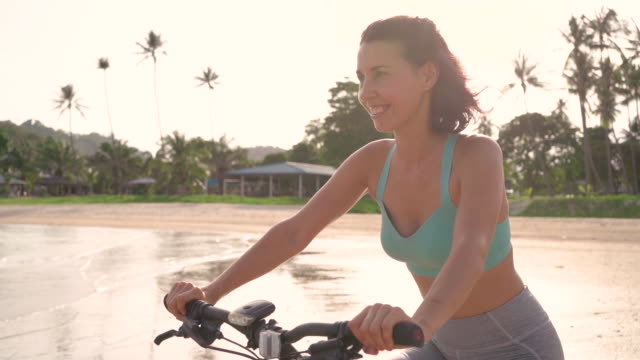 wonan riding bicycle in slow motion on the beach - palm tree stock videos & royalty-free footage