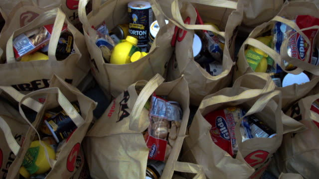 vídeos y material grabado en eventos de stock de wonder bread is some of the items given to people for their holiday food baskets outside the little havana offices of camacol, the latin american... - latin america