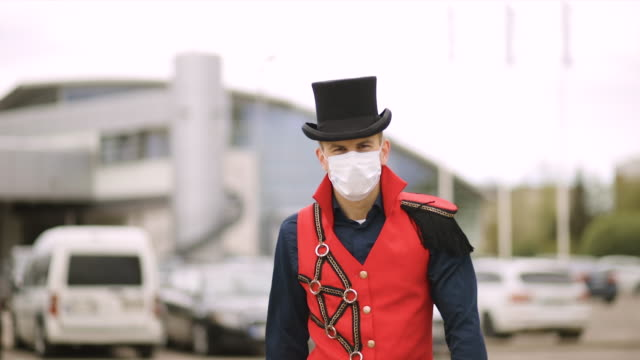 wonderful magician in black top hat and red stage costume wears medical face mask and walks at camera - top hat stock videos & royalty-free footage