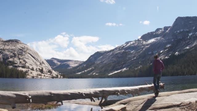 Wonderlust solo female traveler enjoying tranquility of secluded lake in spring