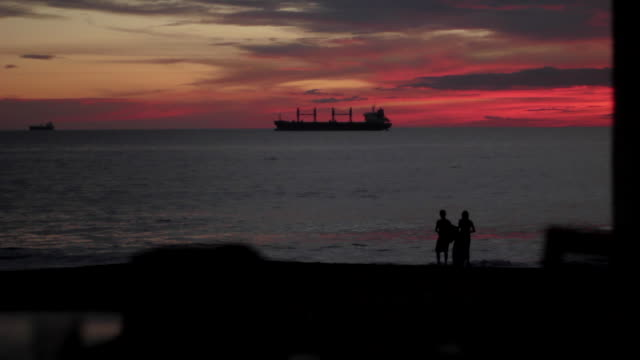wonderlust - sunset over coastline with skim-boarders silhouetted against ocean - skimboarding stock videos & royalty-free footage