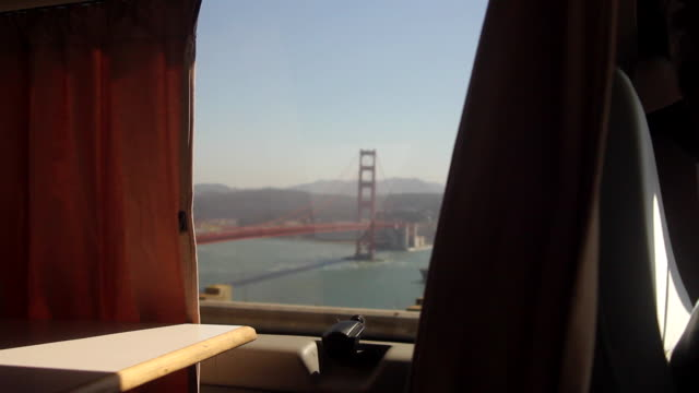 wonderlust - usa, road trip, golden gate bridge through window of campervan - san francisco california stock-videos und b-roll-filmmaterial