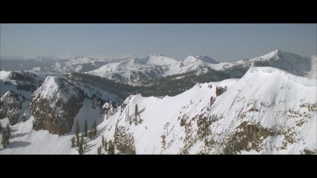 vídeos de stock, filmes e b-roll de aerial wood and mountain range in winter - formato letterbox