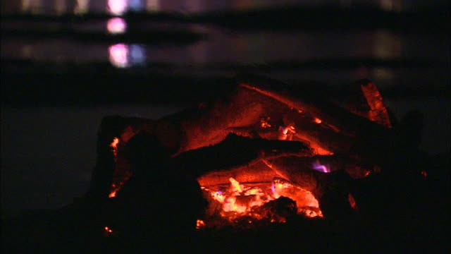 A wood campfire burns on the shore while a cremation takes place across the river.