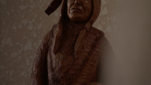 a wood carving of a native american man shows craftsmanship. - statue stock-videos und b-roll-filmmaterial
