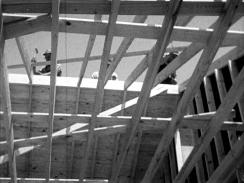 Wood frame building under construction w/ men hammering on roof LA TU Carpenters on roof framing VS Two AfricanAmerican brick masons on wall catching...