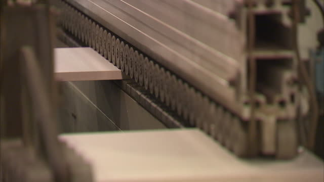 Wood panel moving through conveyor belt in a furniture factory