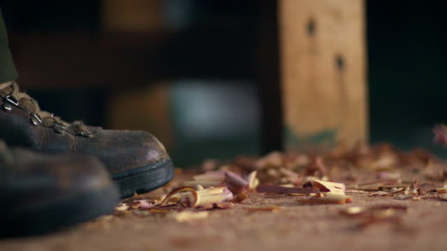 vídeos y material grabado en eventos de stock de wood shavings fall to the floor of a workshop where a person in heavy-duty work boots is standing. - carpintería