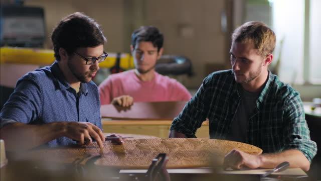 vidéos et rushes de wood shop craftsman points out design details of custom longboard to pupil - enseigne