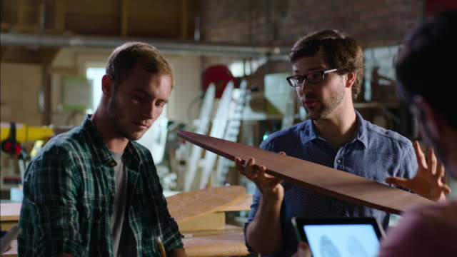 Wood shop owner teaches young workers about designing and crafting custom skateboards