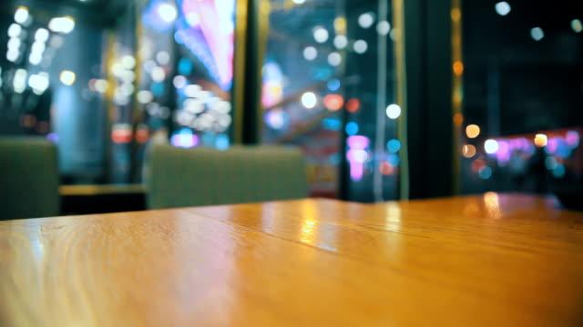 vídeos y material grabado en eventos de stock de mesa de madera con luz borrosa en la noche - pub