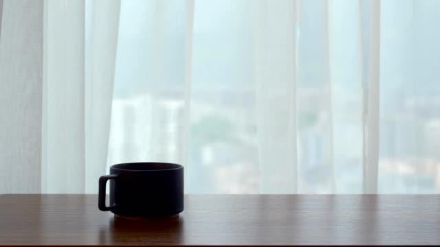 窓の前にコーヒーカップがあるウッドテーブル - coffee cup点の映像素材/bロール