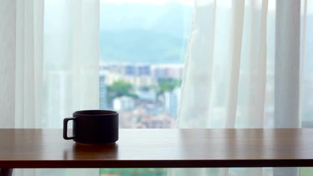 Houten tafel met koffie kopje voor venster