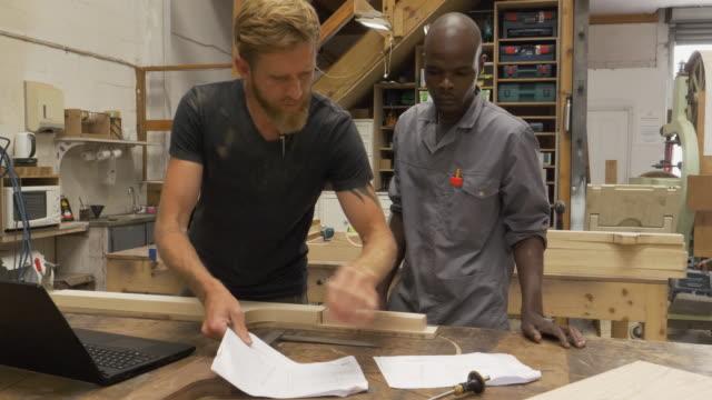 vidéos et rushes de wood workers in a furniture factory - apprenti