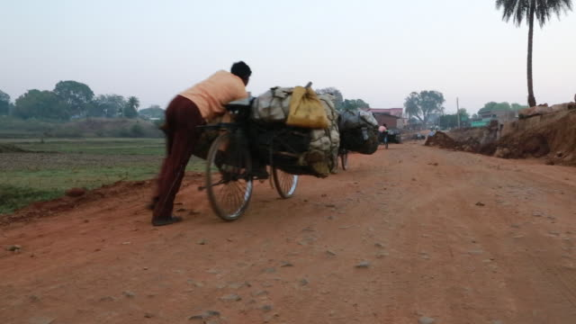 woodcarrier pushing bike on dusty road, dumka, india - dirt road stock videos and b-roll footage