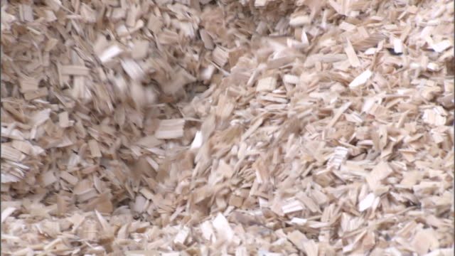 woodchips funnel down a vat in a paper mill. - paper mill stock videos and b-roll footage