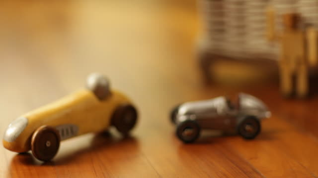 vidéos et rushes de a wooden and tin race car on parquet floor - jouet