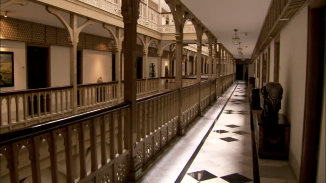 a wooden balustrade runs the length of a hallway in the taj mahal hotel mumbai available in hd. - tile stock videos & royalty-free footage