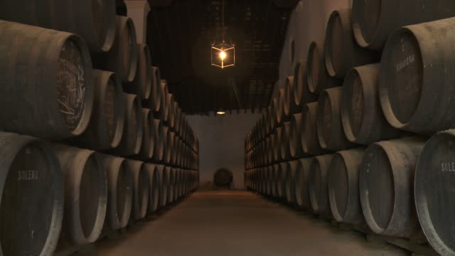 Wooden barrels are stacked in a basement cellar in Andalusia.