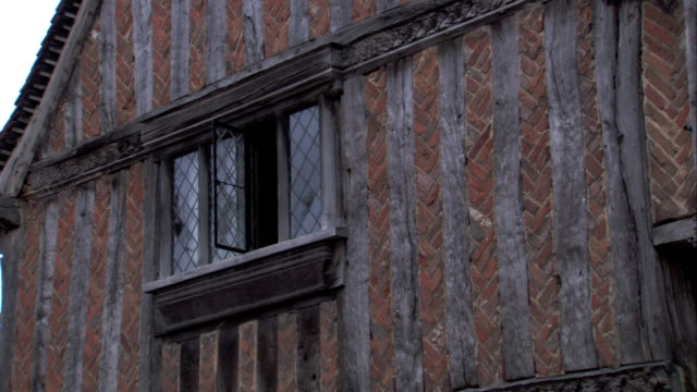 wooden beams frame a medieval cottage window . available in hd. - lavenham stock-videos und b-roll-filmmaterial
