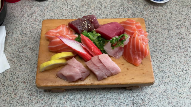 a wooden board of different cuts of sashimi (sushi) sitting on a kitchen counter - seafood stock videos & royalty-free footage