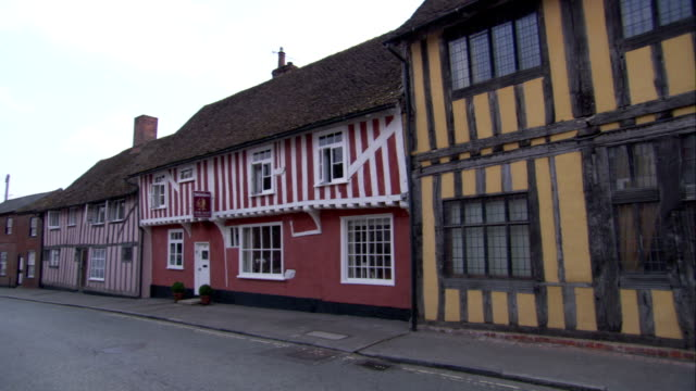 wooden boards frame the windows of medieval houses in lavenham, england. available in hd. - lavenham stock-videos und b-roll-filmmaterial