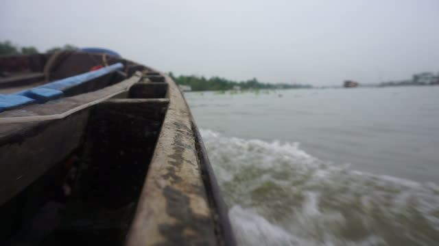 Wooden boat travelling along the Mekong river