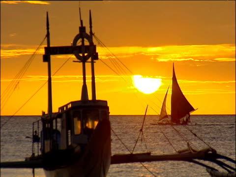wooden boat with stabilising floats bobs on calm sea small sail boat passes behind bright orange sky with setting sun philippines - human limb stock videos & royalty-free footage