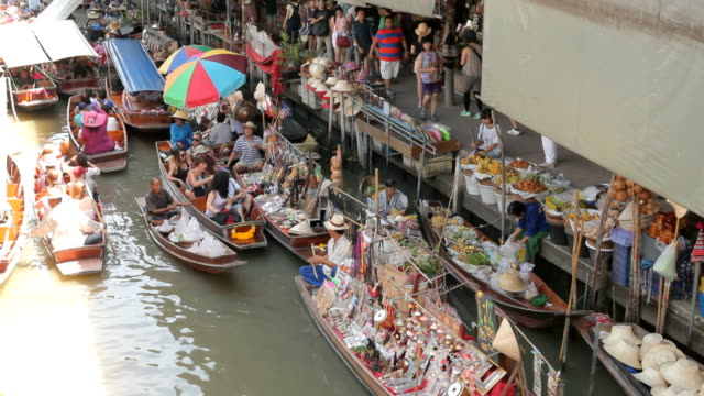 wooden boats busy ferrying people at damnoen saduak floating market - floating market stock videos and b-roll footage