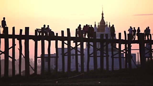 wooden bridge with pedestrians at sunset in myanmar - myanmar stock videos and b-roll footage