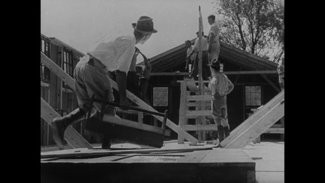 wooden building being constructed carpenters working on roof beams being supervised by male in army uniform building walls being braced - civilian conservation corps stock-videos und b-roll-filmmaterial